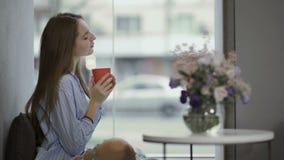 女孩享用咖啡坐窗口基石 股票视频