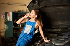 女孩享用她的香烟坐在车库的一辆汽车 免版税库存图片
