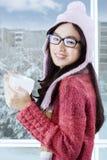 女孩享用温暖的饮料和微笑在照相机 库存照片