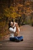 女孩亲吻一只猫在一个公园在秋天 库存图片