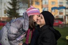 女孩亲吻的母亲少数民族居住区 库存照片