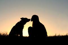 女孩亲吻的狗剪影 免版税库存图片