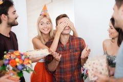 女孩人惊奇为生日做准备 她用人工闭上了他的眼睛 免版税图库摄影