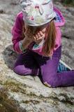 女孩从一条山小河在早期的春天喝 图库摄影