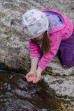 女孩从一条山小河在早期的春天喝 库存图片