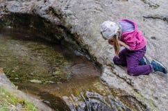 女孩从一条山小河在早期的春天喝 免版税库存图片