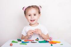 女孩从彩色塑泥猪和兔宝宝雕刻 库存照片