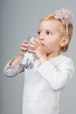女孩从玻璃的饮料水。 免版税库存图片