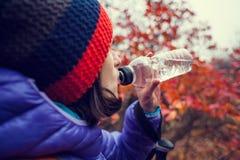 女孩从瓶喝 图库摄影