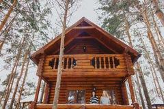 女孩从背景的o一个村庄木房子出来 免版税图库摄影