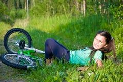 女孩从自行车跌倒了 免版税库存图片