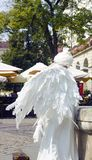 女孩以一个天使的形式在城市 白色活天使雕象 免版税库存照片