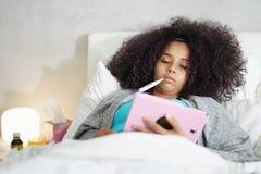 女孩以使用温度计和片剂的热病在床上 库存照片