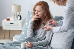 女孩以热病在床上 免版税库存图片