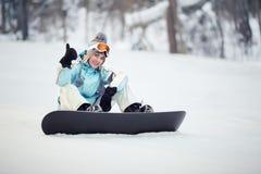 女孩以雪板休息 库存图片