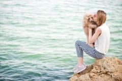 女孩休息与在海的一条狗 库存照片