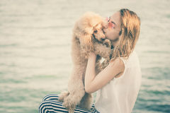 女孩休息与在海的一条狗 免版税图库摄影