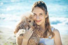 女孩休息与在海的一条狗 库存图片
