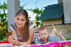 女孩休息以她的一条桃红色毯子的兄弟 库存图片