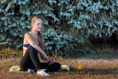 女孩休息的坐草 免版税图库摄影
