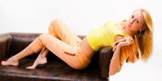 女孩位于的性感的沙发 免版税库存图片