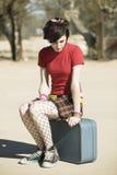 女孩低劣的坐的手提箱 库存图片