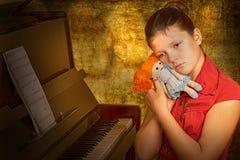 女孩体贴的钢琴演奏家坐在钢琴 免版税库存图片