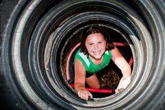 女孩作用被回收的轮胎隧道 免版税库存照片