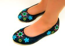 女孩佩带手工制造鞋子 免版税库存图片