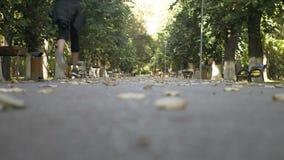 女孩佩带的体育在公园给跑步穿衣在一个秋天晴天- 股票视频