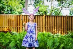 女孩佩带的兔宝宝耳朵和吃红萝卜 免版税库存照片