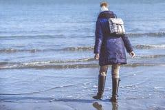 女孩佩带的冬天衣裳在海岸走用bo观看 图库摄影