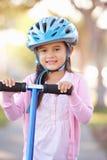 女孩佩带的安全帽骑马滑行车 免版税库存图片