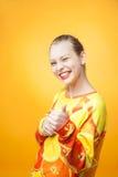 女孩佩带的桔子打印的运动衫 免版税库存图片