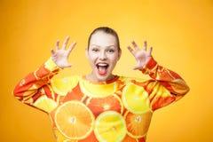 女孩佩带的桔子打印的运动衫 免版税图库摄影