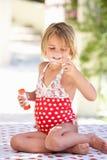 女孩佩带的游泳衣吹的泡影 免版税库存照片