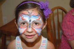 女孩佩带的面孔油漆蝴蝶设计 免版税库存照片