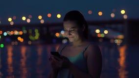 女孩使用一个智能手机,当走在夜海滩时 股票录像