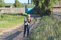 女孩使用一台数字照相机的少年摄影师在农村乡下 免版税库存照片