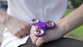女孩使用与一个转动的玩具,旋转在她的手上 女孩twirks锭床工人露天 股票视频