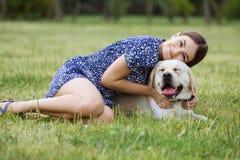 女孩使用与在草的一条狗 培训狗 免版税库存图片