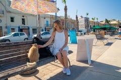 女孩使用与猫和吃晚餐在马耳他的Marsaxlokk渔村 免版税图库摄影
