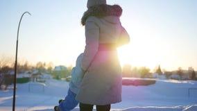 女孩使用与婴孩在冬时的日落 盘旋握手 股票录像