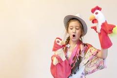 女孩使用在木偶剧院的8年 反对轻的背景 复制空间 库存图片