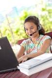 女孩使用年轻人的耳机膝上型计算机 库存图片