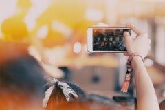 女孩使用智能手机拍照片在音乐会 免版税图库摄影