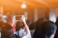 女孩使用智能手机拍照片在音乐会 库存图片