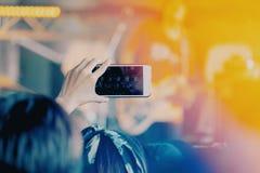 女孩使用智能手机拍照片在音乐会 免版税库存图片