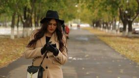 女孩使用智能手机的米黄外套的在街道 影视素材