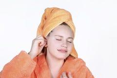 女孩使用棉花棒的抓痕耳朵 表现出在面孔的享受 免版税图库摄影